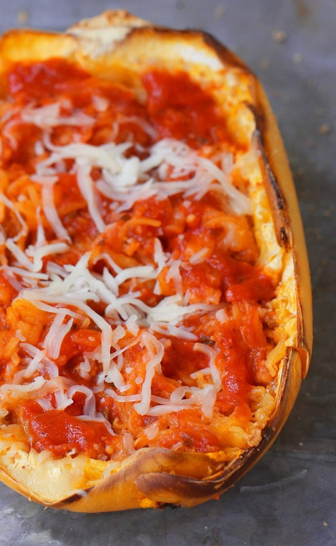 Cheesy Baked Spaghetti Squash Parmigiana - 5 ingredients, simple comfort food... A satisfying & super healthy weeknight meal, without all the extra fat and calories weighing you down. @choccoveredkt http://chocolatecoveredkatie.com/2016/03/10/spaghetti-squash-parmigiana-recipe-healthy-dinner/