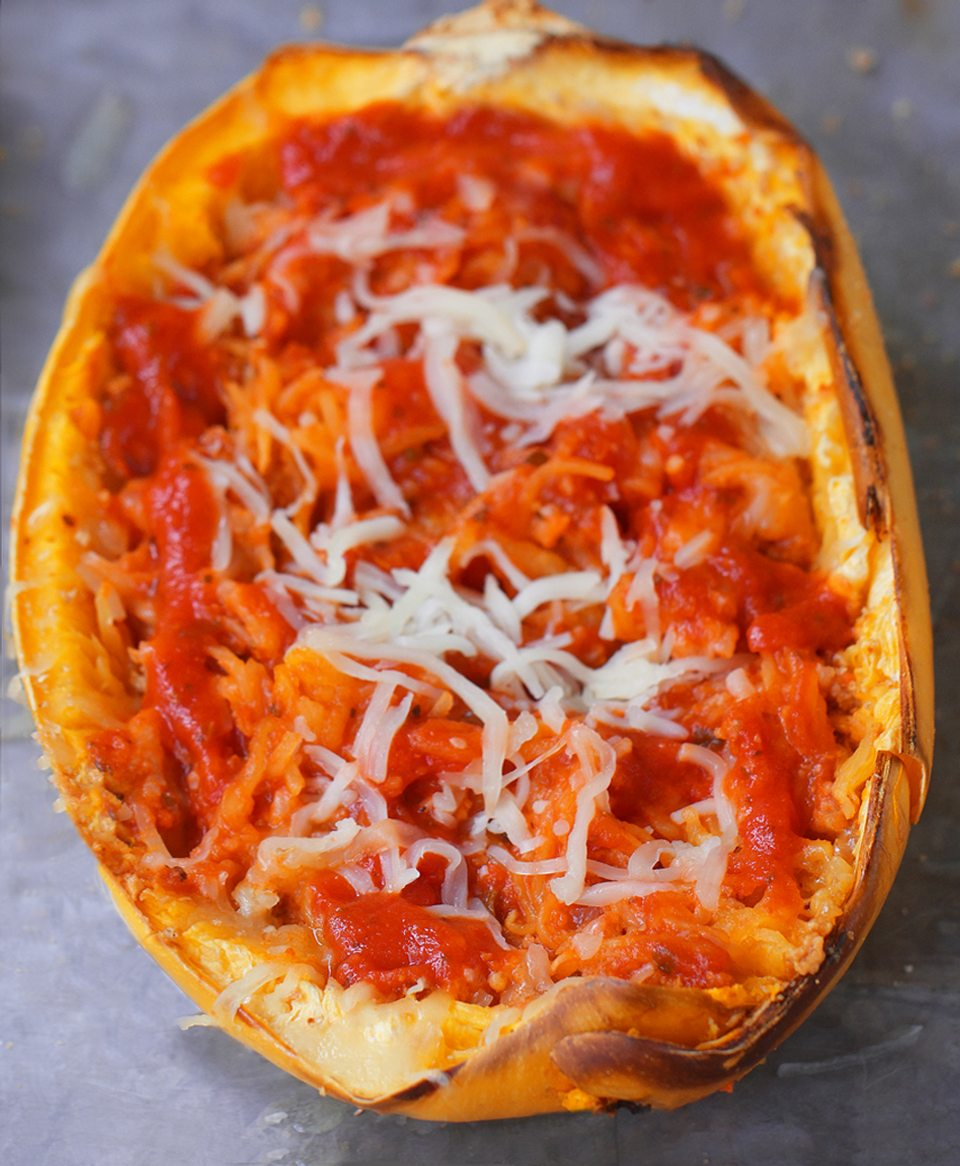 Cheesy Baked Spaghetti Squash Parmigiana - 5 ingredients, simple comfort food... A satisfying & super healthy weeknight meal, without all the extra fat and calories weighing you down. @choccoveredkt https://chocolatecoveredkatie.com/2016/03/10/spaghetti-squash-parmigiana-recipe-healthy-dinner/